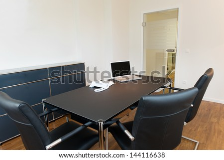 Interior of empty dentist's office with laptop and landline phone on desk