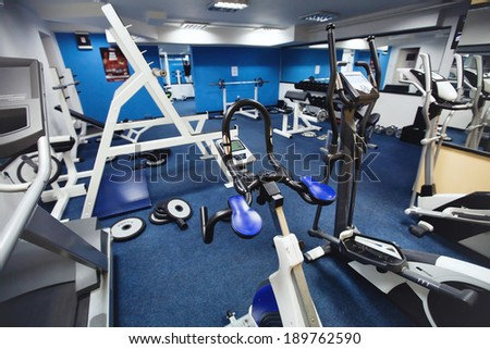 interior of fitness center, training on the bicycle - stock photo