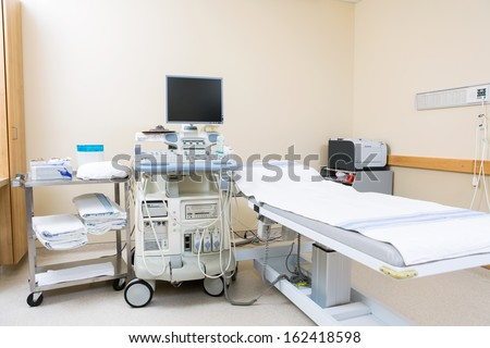 Interior of hospital room with ultrasound machine and bed