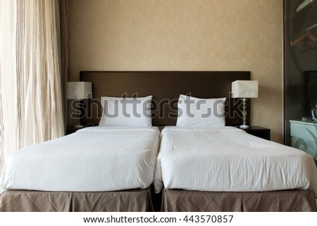 Interior of hotel bedroom with twin beds putting together