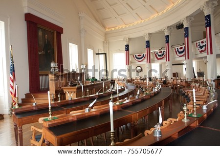 Interior of Illinois House of Representative chamber, with circular lines of seats, the portrait of Abraham Lincoln's and many American flags. Old State Capitol - Springfield, Illinois, USA. Sept 2009