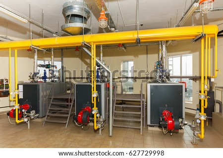 Interior of industrial gas boiler house with many pipes and boilers.