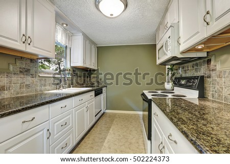 Interior Of Kitchen Room With White Cabinets Granite Tops Natural Stone Back Splash Tile