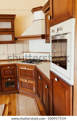 Interior of kitchen with wooden built in cabinets, oven and range with white counter tops and wood floors.