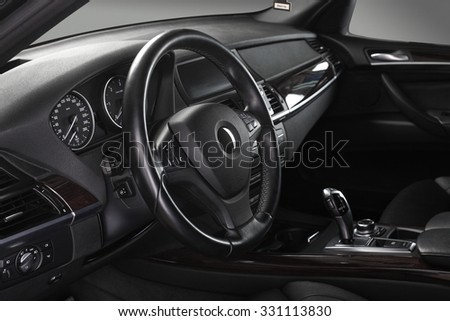 Interior of leather passenger compartment of the car in dark tones. - stock photo