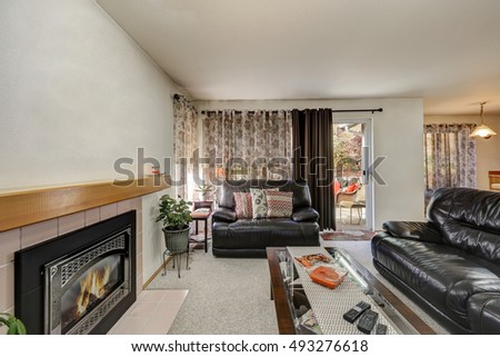 Interior of living room with luxury leather sofas, wall mounted fireplace and exit to the back yard. Northwest, USA