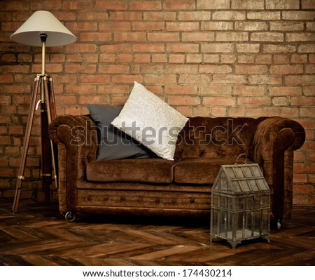 Interior of loft with velvet sofa and lamp - stock photo