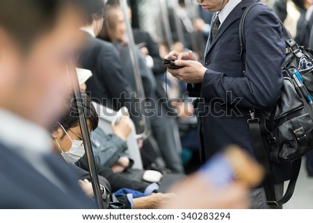 Interior of moder Tokyo metro with passengers on seats and businessmen using their cell phones. Corporate business people commuting to work by public transport. Horizontal composition. - stock photo