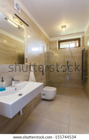 Interior of modern bathroom with travertine walls