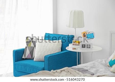Interior of modern bedroom with cozy armchair and bed