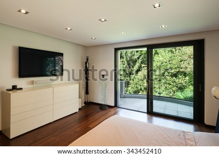 Interior of modern house, bedroom with television - stock photo