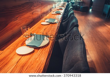 Interior of modern restaurant with table, chairs and tableware - stock photo