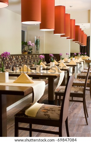 Interior of modern restaurant with the covered tables, wooden furniture, red lamps and flowers