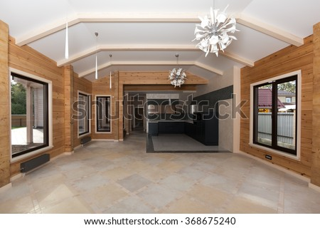 Interior of new wooden eco house built from cedar. Spacious studio. Fashionable modern black kitchen. Italian design white chandeliers.