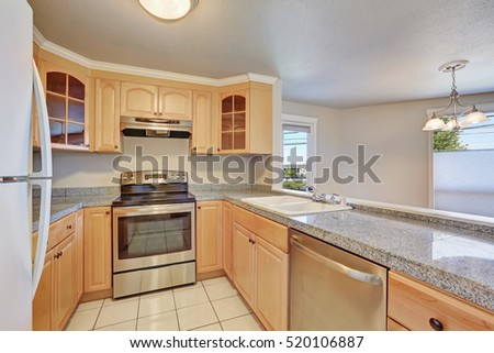 Interior of nice u-shaped kitchen room with light wood cabinets , granite counter tops. Northwest, USA
