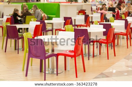 Interior of public dining area with colourul plastic chairs and tables - stock photo
