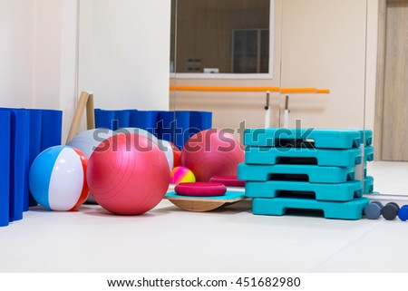 interior of rehabilitation gym, with equiment: balls, mats, steps, mirror - stock photo