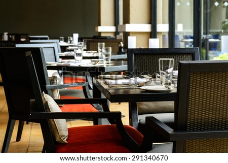 interior of restaurant with black wooden table and chair close to window - stock photo