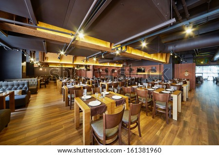 Interior of restaurant with wooden furniture and walls of red bricks - stock photo