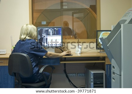 Interior of scanner room and doctor working with X-ray CT scanner. - stock photo