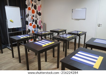 Interior of small business meeting room with decks and flipchart. Nobody