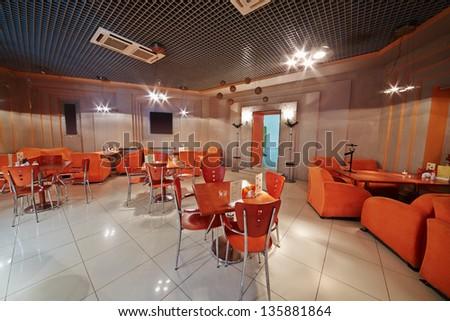 Interior of small empty cafe in orange tones - stock photo