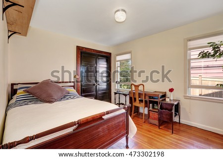 Interior of small white bedroom with vintage desk. Northwest, USA