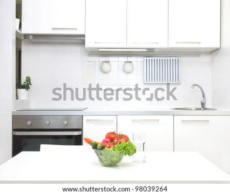 interior of small white kitchen with fresh vegetables on the table - stock photo