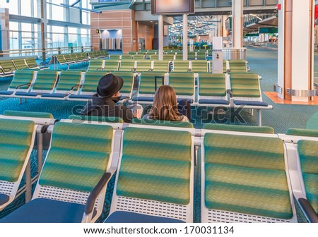Interior of the airport terminal with people, couple waiting for the flight. - stock photo