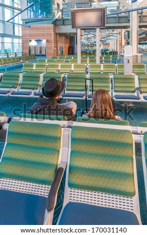 Interior of the airport terminal with people, couple waiting for the flight. Vertical. - stock photo