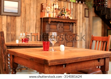 Interior of the cafe, tables, chairs and a wooden wall