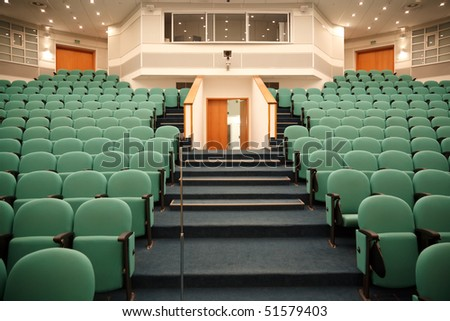 Interior of the hall for holding conferences. Rows of chairs for the audience and stage. Focus on the chairs. - stock photo