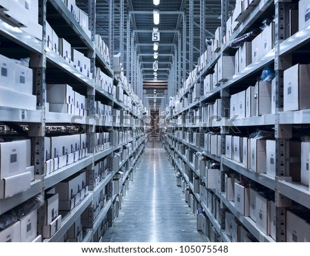 Interior of the new and modern warehouse space in a well lit large room. Rows of shelves with boxes - stock photo