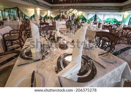 Interior of the restaurant with nicely served and decorated tables of the luxury resort. - stock photo