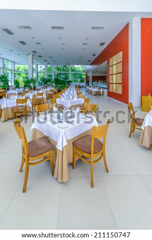 Interior of the tropical, caribbean restaurant with nicely served and decorated tables at the luxury resort. Vertical.
