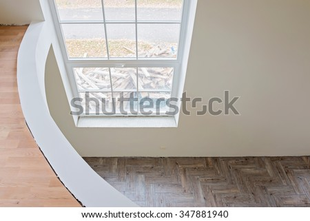 Interior of unfinished living room with tile wooden floors and big window. View from balcony. - stock photo