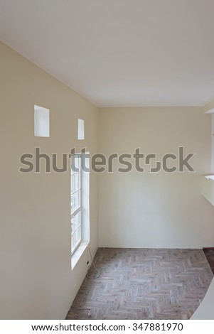 Interior of unfinished living room with tile wooden floors and big windows. View from balcony. - stock photo