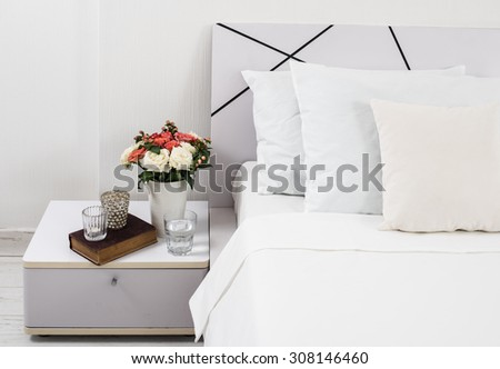 Interior of white bedroom, new linens on the bed, the room at the hotel. Bedside table decor and pillows closeup. - stock photo