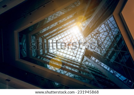Interior photo of modern building atrium with shining sun - stock photo