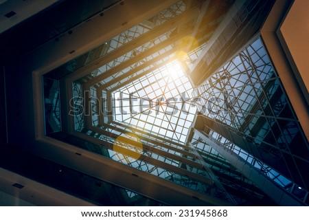 Interior photo of modern building atrium with shining sun - stock photo