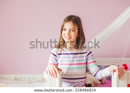 Interior portrait of a cute little girl in her room - stock photo