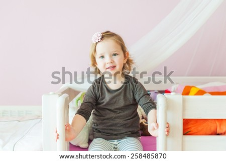 Interior portrait of a cute toddler girl in her room - stock photo