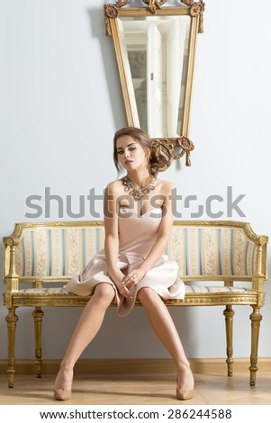 interior portrait of pretty brunette girl with elegant style and precious necklace sitting on antique sofa in aristocratic room with mirror on her back  - stock photo