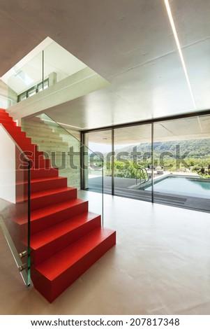 Interior, red staircase in modern villa - stock photo