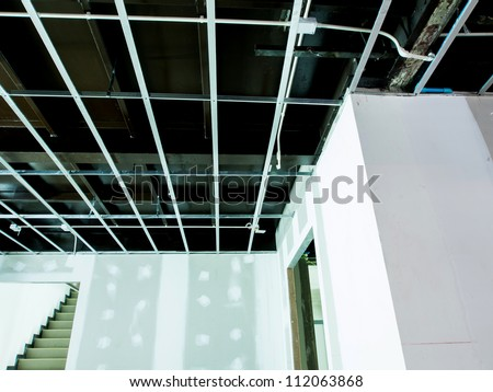 Interior remodeling work on an existing commercial building - ceiling is being prepared for electricity system- with stair and wall are prepared for painting - stock photo