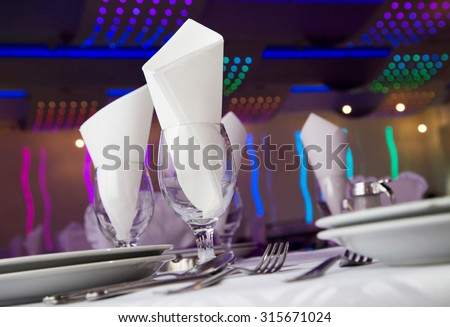 Interior set up of table with glasses, napkins and silverware - stock photo