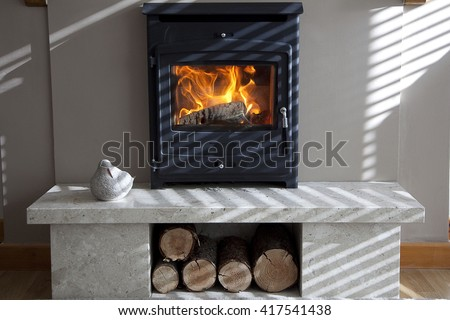 interior shot of log burner and fireplace with shadows from morning sun - stock photo