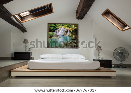 interior view of a bedroom in the attic room. Bedroom in the attic with a picture of nature with a waterfall over the bed. Romantic bedroom with a romantic painting on the wall. Empty roof bedroom.
