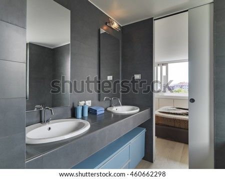 interior view of a modern bathroom in foreground two Vanity basin overlooking on the bedroom