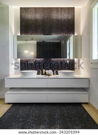 interior view of a modern bathroom whose floor is made in mosaic tiles and parquet,  in foreground the white furniture for two washbasins - stock photo
